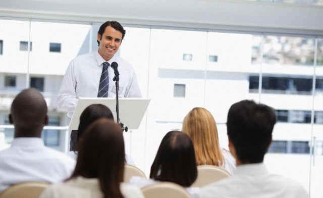 Black haired businessman smiling as he is being watched by an audience --- Image by © Wavebreak Media Ltd./Corbis